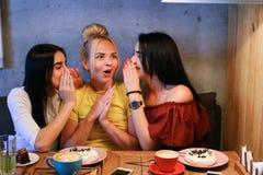 Três o sorriso fêmea bonito no café, conversa, diz segredos, come, d Foto de Stock