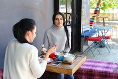 Três o sorriso fêmea bonito no café, conversa, diz segredos, come, d Imagem de Stock Royalty Free