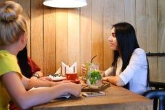 Três o sorriso fêmea bonito no café, conversa, diz segredos, come, d Fotografia de Stock