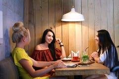 Três o sorriso fêmea bonito no café, conversa, diz segredos, come, d Fotos de Stock