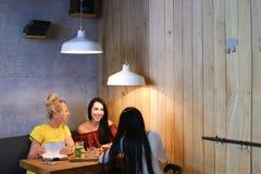 Três o sorriso fêmea bonito no café, conversa, diz segredos, come, d Fotografia de Stock Royalty Free