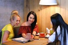 Três o sorriso fêmea bonito no café, conversa, diz segredos, come, d Fotos de Stock Royalty Free