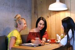 Três o sorriso fêmea bonito no café, conversa, diz segredos, come, d Imagem de Stock