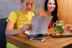 Três o sorriso fêmea bonito no café, conversa, diz segredos, come, d Foto de Stock Royalty Free