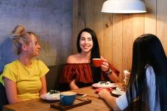 Três o sorriso fêmea bonito no café, conversa, diz segredos, come, d Imagens de Stock