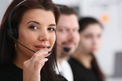 Três operadores do serviço do centro de chamada no trabalho foto de stock
