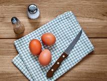 Três ovos bege da galinha em um pano fotos de stock royalty free