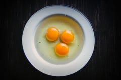 Três ovos crus na placa de metal branco Imagem de Stock Royalty Free