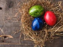 Três ovos da páscoa coloridos em um ninho Imagens de Stock Royalty Free
