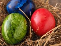 Três ovos da páscoa coloridos em um ninho Foto de Stock