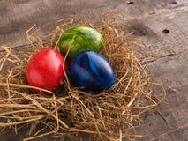 Três ovos da páscoa coloridos em um ninho Fotos de Stock