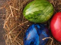 Três ovos da páscoa coloridos em um ninho Imagem de Stock