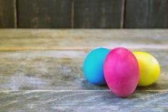 Três ovos da páscoa coloridos na tabela de madeira Easter feliz Imagens de Stock Royalty Free