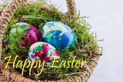 Três ovos da páscoa em uma cesta com musgo Fotografia de Stock