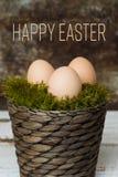 Três ovos da páscoa em uma cesta do musgo, conceito feliz de easter, fundo retro da Páscoa Fotos de Stock