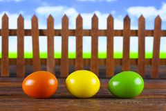 Três ovos da páscoa no fundo de madeira da tabela e da natureza Imagem de Stock