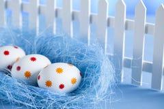 Três ovos da páscoa no ninho e na cerca branca Foto de Stock