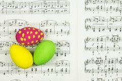 Três ovos da páscoa pintados decorativos na folha com notas da música como o fundo foto de stock