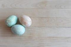 Três ovos da páscoa pintados no fundo de madeira fotos de stock