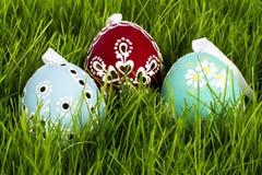 Três ovos de easter pintados mão na grama Imagem de Stock