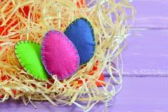 Três ovos de feltro de cores diferentes Fácil e sentiu rapidamente a decoração dos ovos Composição elegante da Páscoa Decoração d fotos de stock royalty free