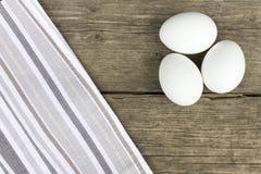 Três ovos de galinha brancos crus na tabela de madeira do vintage velho, coberta com o pano bege listrado fotografia de stock