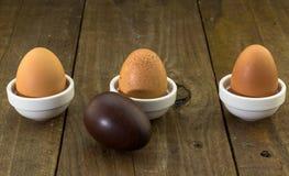 Três ovos de galinha em seguido no fundo de madeira rústico com uma madeira Fotos de Stock Royalty Free