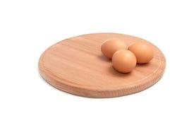 Três ovos e placa redonda. Imagens de Stock