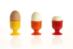 Três ovos em uns copos de ovo coloridos Imagem de Stock