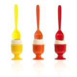 Três ovos em uns copos de ovo coloridos Fotografia de Stock
