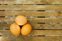 Três ovos na tabela de madeira Fotografia de Stock