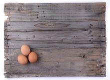 Três ovos no fundo de madeira Fotografia de Stock