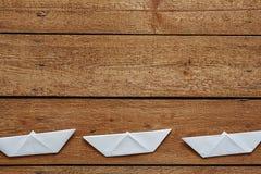 Três paperboats em uma linha fraca na superfície de madeira Imagens de Stock