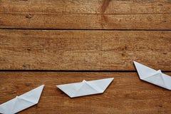 Três paperboats em uma linha vívida na tabela de madeira foto de stock royalty free
