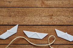 Três paperboats selvagens e uma corda em pranchas de madeira Fotos de Stock Royalty Free