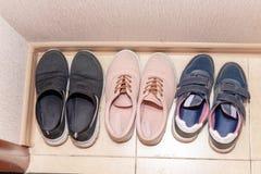 Três pares de calçados casuais - botas, sapatilhas, tênis de corrida no corredor imagem de stock