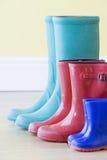 Três pares de Gumboots colorido em uma fileira Foto de Stock