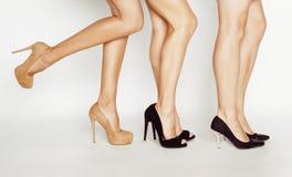 Três pares de pés da mulher na altura colocam saltos sapatas no branco Fotos de Stock