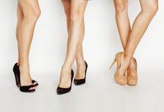 Três pares de pés fêmeas em sapatas dos saltos altos no fundo branco, conceito da mulher do estilo de vida Fotos de Stock