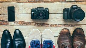Três pares de sapatas e três câmeras Sapatas do negócio, calçados casuais, caminhando botas no conceito de madeira do backgriound Fotos de Stock Royalty Free