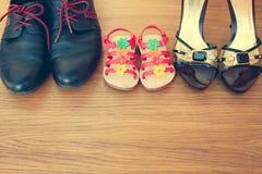 Três pares de sapatas: homens, mulheres e crianças Imagens de Stock