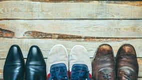 Três pares de sapatas no backgriound de madeira: Sapatas, calçados casuais e caminhada do negócio do conceito das botas de escolh Imagens de Stock