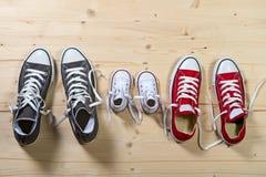 Três pares de sapatas no pai grande, o meio da mãe e o filho ou tamanho pequeno da criança da filha no conceito da unidade da fam Fotografia de Stock