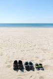 Três pares de sapatilhas estão na areia O conceito do fim de semana Fotografia de Stock Royalty Free