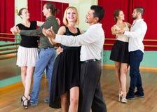 Três pares felizes que dançam o tango Fotografia de Stock