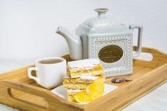 Três partes de torta do limão com fatia de limão e de copo do chá Foto de Stock
