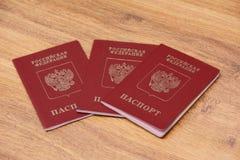 Três passaportes internacionais em um fundo de madeira imagem de stock