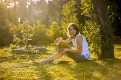 Três patinhos pequenos em uma jovem mulher, sentando-se no jardim, guardando o ramalhete das flores, olhando a câmera Foto de Stock