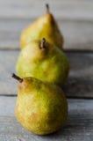 Três peras maduras frescas na fileira Fotografia de Stock