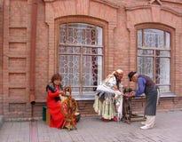 Três pessoas adultas em trajes medievais descrevem artesões no festival fotos de stock